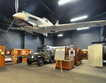 "Hanging above the World War II gallery is a full scale replica Curtis P-40B Warhawk fighter plane painted in the markings of an American Volunteer Group ""Flying Tiger"" aircraft."