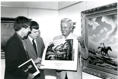 "From left, the museum's director Dick Leet, Jerry Caralstadt and Art Brandeberry, who is holding ""Spring Tryout"" by Thomas Hart Benton, in 1982. Photo courtesy of the Charles H. MacNider Art Museum"