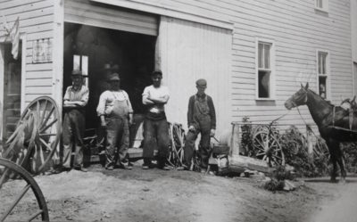 Al Klindt, second from the right wearing a white T-shirt with his arms folded, stands outside his blacksmith shop in Long Grove. Klindt's shop was located across the street from Stockman's Savings Bank when two men robbed it on Dec. 15, 1921. He and other citizens of Long Grove participated in a gun battle that mortally wounded the robbers. Photos courtesy of City of Long Grove, Iowa