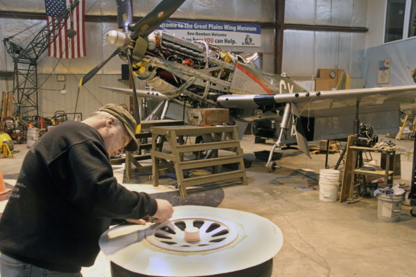 Jim Mason carefully sands a hub for one of Gunfighter's three wheels. The P-51 Mustang built during World War II is on display at the Council Bluffs Municipal Airport and can be seen at airshows. Photo by Mike Whye