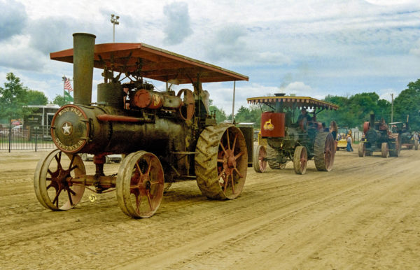 A cavalcade of power, like the 1913 Wood Brothers steam engine tractors operated by Bob and Melinda Stevens in this picture, is always on display at the Midwest Old Threshers Reunion. Photo courtesy of Midwest Old Threshers Reunion